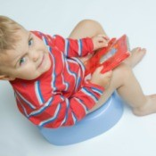 Toddler boy sitting on potty chair holding a book