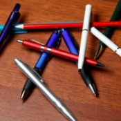 Pile of assorted pens on a wooden table