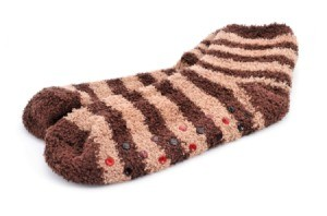 A pair of fuzzy socks with rubber dots on the bottom to help stop slipping