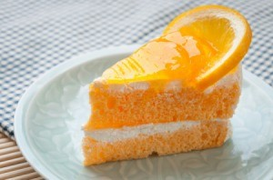 Slice of orange cake on a white plate (topped with an orange slice)