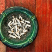 Ashtray full of cigarette butts on a painted red wooden table.