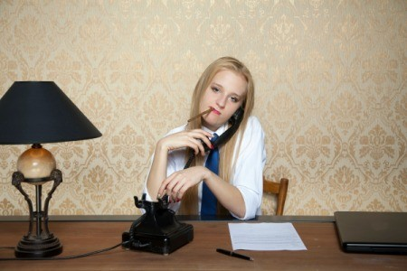 Woman talking on phone will smoking a cigarette in front of vinyl wallpaper