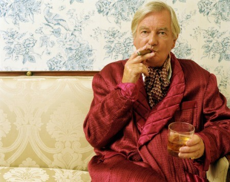Man in dressing robe smoking cigar with wallpaper in the background