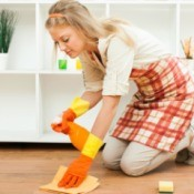 Woman cleaning floor with orange spray bottle and rag
