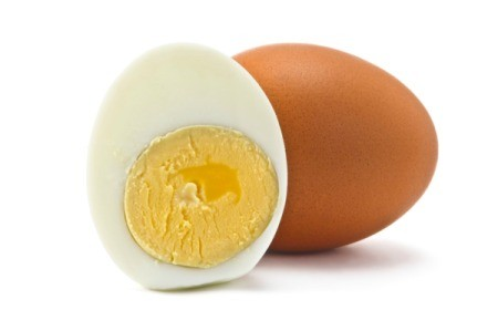 One brown egg and one half of a peeled hard boiled egg against a white background