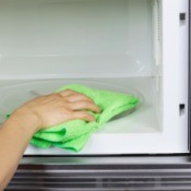 Hand cleaning inside of a microwave oven with a rag