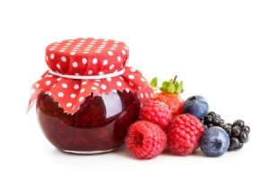 A jelly jar full of red jam with a red and white cloth on top. and fresh raspberries, blueberries, and blackberries beside it.