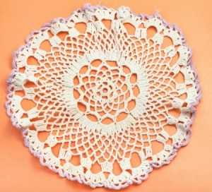 White doily with purple edges against an orange background.  Doily does not appear to be starched
