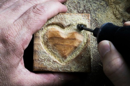 Close up of rotary tool being used to carve a heart in a wood block