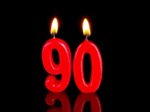 "Lit candles in the shape of ""90"" against a white background"