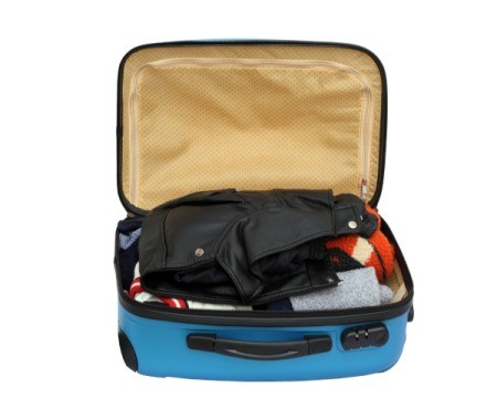 Small packed suitcase open against a white background