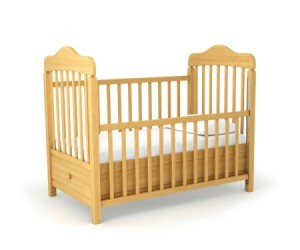 Wooden crib with fitted sheet on a white background