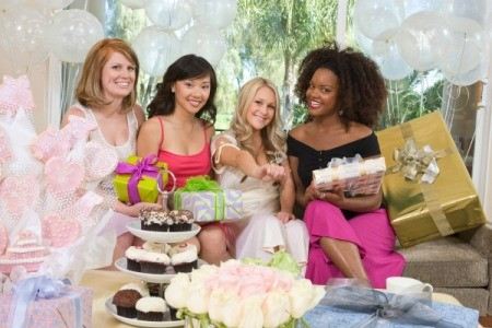 Four women sitting on a couch at an engagement party surrounded by cupcakes, treats and gifts.  One is wearing a gigantic plastic diamond ring