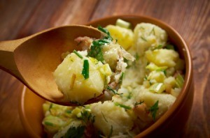 Spoon holding german potato salad over a bowl of same.