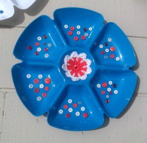 Serving trays decorated with buttons and a crocheted center, in red, white and blue.