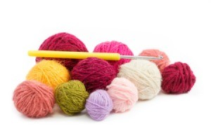 Several different color rolls of yarn with a crochet hook against a white background