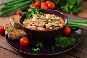 bowl of paprika chicken with bread and veggies