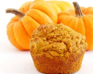 Pumpkin Spice Cupcake  in front of several small pumpkins
