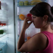 Woman holding nose while standing in front of open refrigerator door