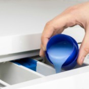 Hand pouring fabric softener into washing machine compartment