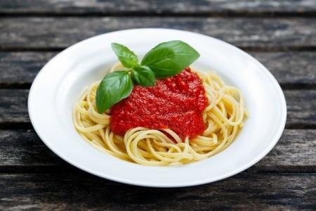 White pasta bowl with spaghetti pasta, marinara sauce and a sprig of basil