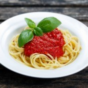 White pasta bowl with spaghetti pasta, marinara sauce and a sprig of basil
