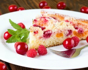 Dump cake (cake with canned mixed fruit  in it) on a white plate.