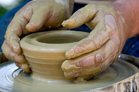 Hands forming a bowl on a pottery wheel