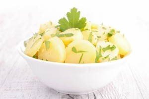 Potato salad that does not have mayo in a white bowl