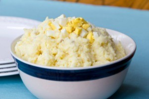 Mashed Potato salad in a white bowl with blue rim.