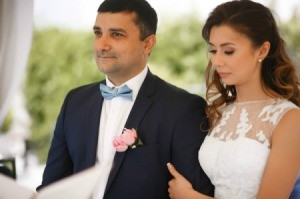 Bride and Groom.  Groom is wearing a blue bow tie and pink boutonniere
