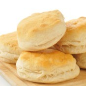 Several biscuits piled on a cutting board against a white background