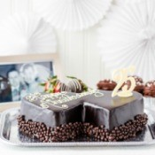 "Double heart shaped chocolate cake that says ""Wedding Anniversary"" with a 25 decoration.  Black and white wedding picture in the background"