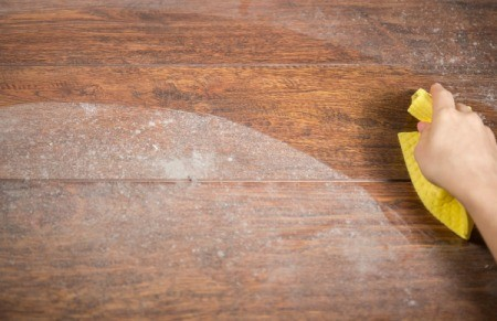 Hand wiping white residue off wooden floor