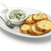 Dish of spinach artichoke dip and toasted baguette slices on a plate