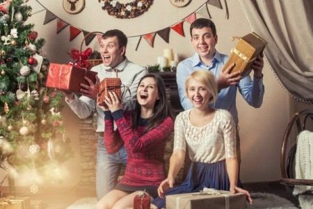 Two men and two women laughing and shaking presents by a Christmas tree.