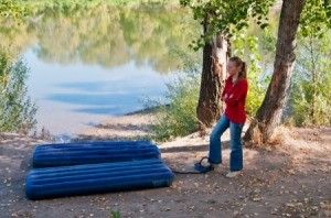 Woman pumping up air mattress in the woods