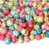 Red, white and blue colored popcorn spilled out onto white surface