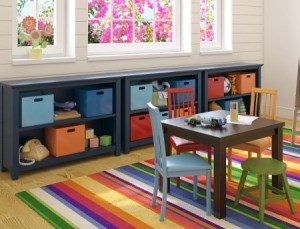 An playroom with bins and toys arranged on shelves