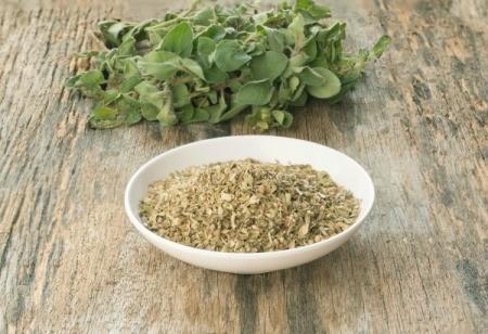 Fresh oregano and bowl of dried oregano on wooden surface
