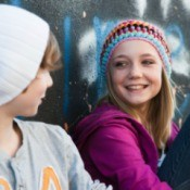 Young teen-age girl and boy sitting against a wall