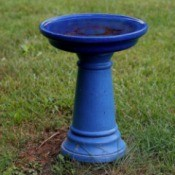 Blue painted bird bath in grass