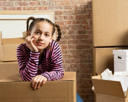 Young thoughtful girl resting with chin in hand amongst moving boxes