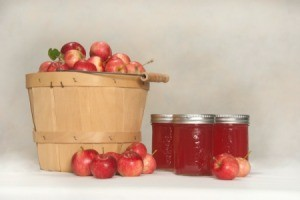 Basket of crab apples next to three jars of crab apple jelly and loose crab apples.