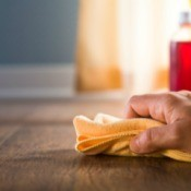 Close up of hand wiping the floor with bottle cleaner in the background