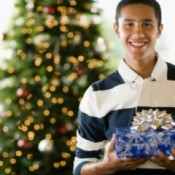 Teenage boy holding rapped Christmas present in front of decorated tree