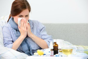 Woman holding kleenex to nose with a variety of cold remedies in front of her