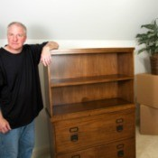 Man standing next to heavy hutch and boxes on carpet