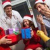 Four adults in santa hats laughing and exchanging brightly colored gifts