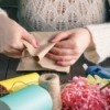 Woman hands folding paper surrounded by various craft supplies